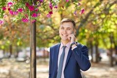 Ωραίος νεαρός άνδρας που εργάζεται στο πάρκο και που θέτει στη κάμερα χρυσή ιδιοκτησία βασικών πλήκτρων επιχειρησιακής έννοιας πο Στοκ Φωτογραφία