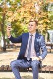 Ωραίος νεαρός άνδρας που εργάζεται στο πάρκο και που θέτει στη κάμερα χρυσή ιδιοκτησία βασικών πλήκτρων επιχειρησιακής έννοιας πο Στοκ Εικόνα
