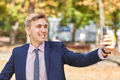 Ωραίος νεαρός άνδρας που εργάζεται στο πάρκο και που θέτει στη κάμερα χρυσή ιδιοκτησία βασικών πλήκτρων επιχειρησιακής έννοιας πο Στοκ φωτογραφία με δικαίωμα ελεύθερης χρήσης