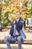 Ωραίος νεαρός άνδρας που εργάζεται στο πάρκο και που θέτει στη κάμερα χρυσή ιδιοκτησία βασικών πλήκτρων επιχειρησιακής έννοιας πο Στοκ φωτογραφίες με δικαίωμα ελεύθερης χρήσης