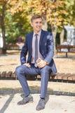 Ωραίος νεαρός άνδρας που εργάζεται στο πάρκο και που θέτει στη κάμερα χρυσή ιδιοκτησία βασικών πλήκτρων επιχειρησιακής έννοιας πο Στοκ Εικόνες