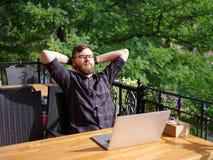 Ωραίος νεαρός άνδρας που εργάζεται στο lap-top καθμένος υπαίθρια χρυσή ιδιοκτησία βασικών πλήκτρων επιχειρησιακής έννοιας που φθά Στοκ Φωτογραφία