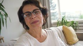 Ωριμάστε τη γυναίκα στα γυαλιά που χαμογελά ενώ έχοντας την τηλεοπτική κλήση φιλμ μικρού μήκους