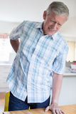 Ωριμάστε το άτομο που πάσχει από τον πόνο στην πλάτη ταυτόχρονα ξεπερνώντας την έδρα Α Στοκ εικόνα με δικαίωμα ελεύθερης χρήσης