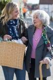 Ωριμάστε το γείτονα που βοηθά την ανώτερη γυναίκα για να φέρει τις αγορές στοκ εικόνα