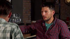 Ωριμάστε το γενειοφόρο άτομο που μιλά στο φίλο του πίνοντας την μπύρα στο μπαρ απόθεμα βίντεο