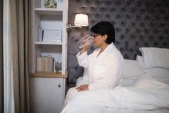 Ωριμάστε το πόσιμο νερό γυναικών καθμένος στο κρεβάτι Στοκ εικόνα με δικαίωμα ελεύθερης χρήσης