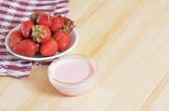 Ωριμασμένες φράουλες σε ένα πιατάκι, που στέκεται σε έναν ξύλινο πίνακα Στοκ Φωτογραφίες