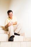 Ωριμασμένο άτομο τον οξύ κοινό πόνο γονάτων που κάθεται που υφίσταται στα σκαλοπάτια Στοκ Εικόνες