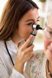 Ωτοσκόπιο εκμετάλλευσης γιατρών και εξέταση του αυτιού της ανώτερης γυναίκας στοκ φωτογραφίες με δικαίωμα ελεύθερης χρήσης