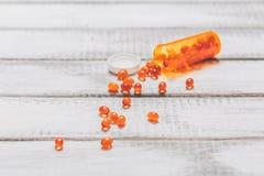 Ω 3与药瓶的鱼油胶囊在白色木桌上 胳膊关心健康查出滞后 库存照片