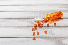 Ω 3与药瓶的鱼油胶囊在白色木桌上 胳膊关心健康查出滞后 免版税库存照片