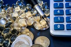 Ω 3,与欧洲硬币的黄色药片 库存图片