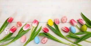 2 όλα τα αυγά Πάσχας έννοιας νεοσσών κάδων ανθίζουν τη χλόη χρωμάτισαν τις τοποθετημένες νεολαίες Οι ρόδινα τουλίπες και τα αυγά  Στοκ εικόνες με δικαίωμα ελεύθερης χρήσης