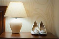 Όμορφα άσπρα παπούτσια από τη νύφη με έναν λαμπτήρα Στοκ Εικόνες