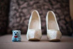 Όμορφα άσπρα παπούτσια από τη νύφη με το teddybear Στοκ Φωτογραφίες