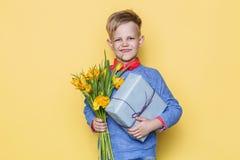 Όμορφα δέσμη λουλουδιών εκμετάλλευσης αγοριών και κιβώτιο δώρων βαλεντίνος ημέρας s Γενέθλια μητέρα s ημέρας Πορτρέτο στούντιο πέ Στοκ εικόνα με δικαίωμα ελεύθερης χρήσης