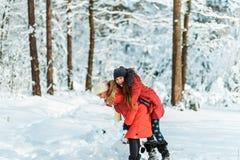 Όμορφα έφηβη που έχουν τη διασκέδαση έξω σε ένα ξύλο με το χιόνι το χειμώνα Φιλία και ενεργός έννοια ζωής στοκ εικόνα με δικαίωμα ελεύθερης χρήσης