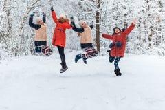 Όμορφα έφηβη που έχουν τη διασκέδαση έξω σε ένα ξύλο με το χιόνι το χειμώνα Φιλία και ενεργός έννοια ζωής στοκ φωτογραφίες