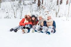 Όμορφα έφηβη που έχουν τη διασκέδαση έξω σε ένα ξύλο με το χιόνι το χειμώνα Φιλία και ενεργός έννοια ζωής στοκ φωτογραφία με δικαίωμα ελεύθερης χρήσης
