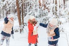 Όμορφα έφηβη που έχουν τη διασκέδαση έξω σε ένα ξύλο με το χιόνι το χειμώνα Φιλία και ενεργός έννοια ζωής στοκ εικόνες
