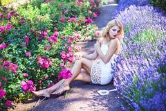 Όμορφα αισθησιακά lavender και τριαντάφυλλα συνεδρίασης κοριτσιών ανθίζοντας πλησίον Στοκ φωτογραφία με δικαίωμα ελεύθερης χρήσης