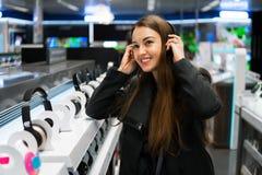 Όμορφα ακουστικά δοκιμής γυναικών στο σύγχρονο κατάστημα στοκ φωτογραφίες με δικαίωμα ελεύθερης χρήσης