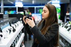 Όμορφα ακουστικά δοκιμής γυναικών στο σύγχρονο κατάστημα στοκ φωτογραφίες