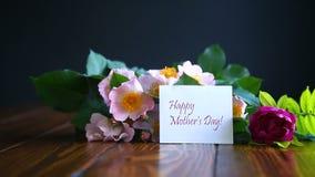 Όμορφα ανθίζοντας τριαντάφυλλα και μια ευχετήρια κάρτα για τη μητέρα απόθεμα βίντεο