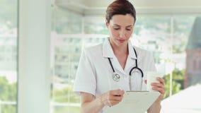 Όμορφα αρχεία ανάγνωσης γιατρών και εξέταση τη κάμερα απόθεμα βίντεο