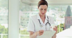 Όμορφα αρχεία ανάγνωσης γιατρών και εξέταση τη κάμερα φιλμ μικρού μήκους