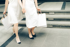 Όμορφα ασιατικά κορίτσια με τις τσάντες αγορών που περπατούν στην οδό Στοκ Φωτογραφίες