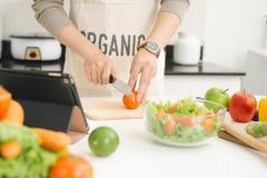 Όμορφα ασιατικά τεμαχίζοντας λαχανικά ατόμων στην κουζίνα Στοκ Φωτογραφία