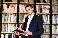 Όμορφα βιβλία εκμετάλλευσης νεαρών άνδρων και χαμόγελο στεμένος στη βιβλιοθήκη Στοκ εικόνες με δικαίωμα ελεύθερης χρήσης