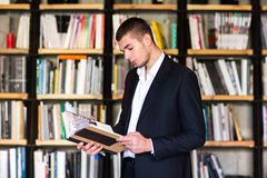Όμορφα βιβλία εκμετάλλευσης νεαρών άνδρων και χαμόγελο στεμένος στη βιβλιοθήκη Στοκ Εικόνα