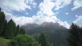 Όμορφα βουνά του βράχου που καλύπτονται από τα άσπρα σύννεφα του μπλε ουρανού με το πράσινο δάσος στο κατώτατο σημείο απόθεμα βίντεο