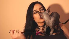 Όμορφα γυναίκα και γατάκι sphynx που παίζουν μαζί με ένα ραβδί φιλμ μικρού μήκους