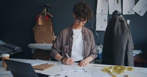Όμορφα ενδύματα σχεδίων σχεδιαστών μόδας κοριτσιών σε χαρτί που δημιουργεί τη νέα συλλογή φιλμ μικρού μήκους
