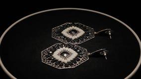 Όμορφα θηλυκά σκουλαρίκια σε μια μαύρη περιστρεφόμενη στάση Κοσμήματα ασφαλίστρου r απόθεμα βίντεο
