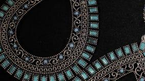 Όμορφα θηλυκά σκουλαρίκια σε μια μαύρη περιστρεφόμενη στάση Κοσμήματα ασφαλίστρου Μακροεντολή απόθεμα βίντεο