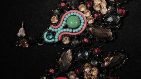 Όμορφα θηλυκά σκουλαρίκια σε μια μαύρη περιστρεφόμενη στάση Κοσμήματα ασφαλίστρου Μακροεντολή φιλμ μικρού μήκους
