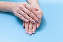 Όμορφα θηλυκά χέρια και ένα μοντέρνο μανικιούρ σε ένα μπλε υπόβαθρο στοκ εικόνες με δικαίωμα ελεύθερης χρήσης