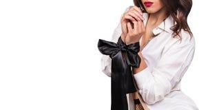 Όμορφα θηλυκά χέρια που δένονται τη μαύρη κορδέλλα που απομονώνεται με στο λευκό Προκλητικό παιχνίδι Στοκ Εικόνες
