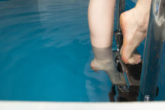 Όμορφα θηλυκά πόδια στα βήματα της λίμνης Στοκ Φωτογραφίες