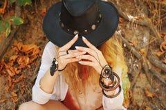 Όμορφα θηλυκά χέρια με τα κομψά βραχιόλια dreamcatcher boho και το μαύρο καπέλο δέρματος στοκ εικόνα