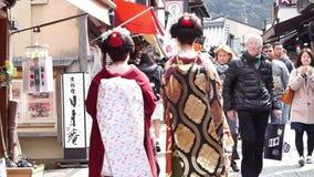 Όμορφα ιαπωνικά γκέισα με το όμορφο κιμονό που περπατούν κατά μήκος της οδού στο Κιότο Ιαπωνία απόθεμα βίντεο