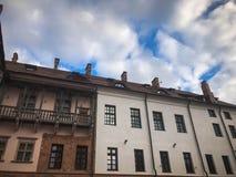 Όμορφα ιστορικά μεσαιωνικά ευρωπαϊκά κτήρια χαμηλός-ανόδου με ένα κόκκινο αέτωμα στεγών κεραμιδιών και ορθογώνια παράθυρα με τους στοκ φωτογραφία