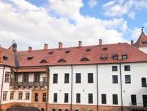 Όμορφα ιστορικά μεσαιωνικά ευρωπαϊκά κτήρια χαμηλός-ανόδου με ένα κόκκινο αέτωμα στεγών κεραμιδιών και ορθογώνια παράθυρα με τους στοκ φωτογραφίες