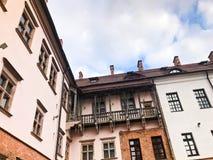 Όμορφα ιστορικά μεσαιωνικά ευρωπαϊκά κτήρια χαμηλός-ανόδου με ένα κόκκινο αέτωμα στεγών κεραμιδιών και ορθογώνια παράθυρα με τους στοκ εικόνες