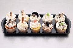 Όμορφα κέικ φλυτζανιών στο μαύρο δίσκο Στοκ Εικόνα